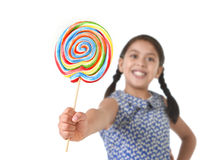 拿着巨大的棒棒糖的拉丁女孩愉快和激动在逗人喜爱的蓝色礼服和马尾糖果概念 库存图片