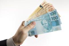 拿着巴西货币的现有量 库存图片