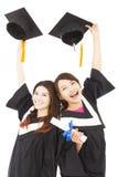 拿着帽子和文凭的两名愉快的年轻毕业生学生 图库摄影