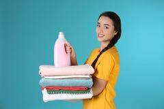 拿着干净的衣裳和洗涤剂的愉快的年轻女人 库存图片