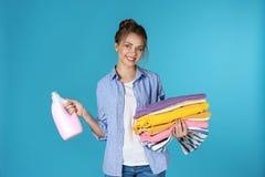 拿着干净的衣裳和洗涤剂的愉快的年轻女人 免版税库存照片