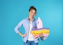 拿着干净的衣裳和洗涤剂的愉快的年轻女人 图库摄影