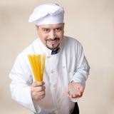 拿着干燥奎奴亚藜意粉和奎奴亚藜五谷的友好的厨师 图库摄影