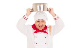 拿着平底深锅的微笑的厨师顶上weraing红色和白色u 库存图片