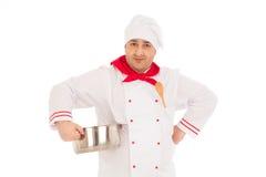 拿着平底深锅的微笑的厨师weraing红色和白色制服 图库摄影