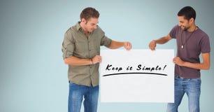 拿着广告牌与的微笑的人保留它简单的文本反对蓝色背景 免版税库存图片