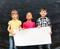 拿着广告的三个逗人喜爱的孩子空的纸板料 免版税库存照片