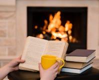 拿着开放书和咖啡的手在壁炉附近 库存图片