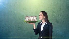 拿着开放手棕榈的少妇现代公寓,在被隔绝的演播室背景 到达天空的企业概念金黄回归键所有权 库存图片