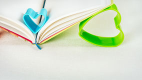 拿着开放日志书的页蓝色和绿色心脏 免版税库存照片