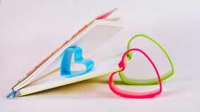 拿着开放日志书的页蓝色红色和绿色心脏 库存图片