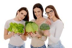 拿着开胃菜、莴苣和硬花甘蓝的三个女孩 免版税库存照片
