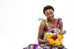 拿着异乎寻常的果子的五颜六色的sundress的可爱的微笑的非洲妇女 免版税图库摄影