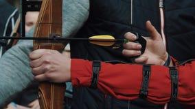 拿着弓箭,教练员的年轻人的手解释射击方法 股票录像