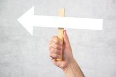 拿着引导的方向箭头标志的人 免版税库存照片