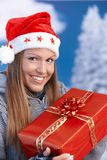 拿着当前圣诞老人妇女的圣诞节帽子 免版税库存照片