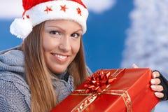 拿着当前圣诞老人妇女的圣诞节帽子 免版税库存图片