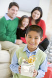 拿着当前常设年轻人的男孩圣诞节 免版税库存图片