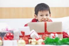 拿着当前箱子的一个可爱的逗人喜爱的小孩的画象和 图库摄影