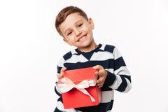 拿着当前箱子的一个愉快的逗人喜爱的小孩的画象 免版税库存照片