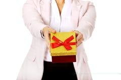 拿着当前箱子的微笑的年轻女商人 免版税库存图片