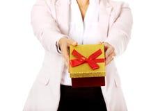 拿着当前箱子的微笑的年轻女商人 库存图片