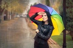 拿着彩虹伞的愉快的秋天妇女检查雨 免版税库存图片