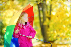 拿着彩虹伞的逗人喜爱的小女孩在美好的秋天天 使用在秋天公园的愉快的孩子 免版税库存照片