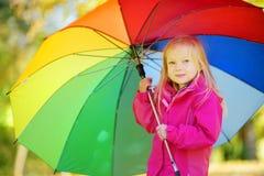 拿着彩虹伞的逗人喜爱的小女孩在美好的秋天天 使用在秋天公园的愉快的孩子 库存照片