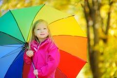 拿着彩虹伞的逗人喜爱的小女孩在美好的秋天天 使用在秋天公园的愉快的孩子 免版税图库摄影