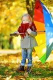 拿着彩虹伞的逗人喜爱的小女孩在美好的秋天天 使用在秋天公园的愉快的孩子 库存图片