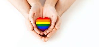 拿着彩虹心脏的男性和女性手 库存图片