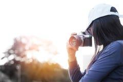 拿着影片照相机的妇女拍摄在自然日落的照片 免版税库存图片