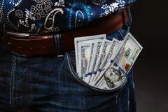 拿着很多金钱的一个人 100美元用不同的口袋,腐败的概念钞票  免版税库存图片
