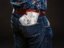 拿着很多金钱的一个人 100美元用不同的口袋,腐败的概念钞票  免版税库存照片