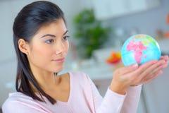 拿着微型地球的妇女 库存图片