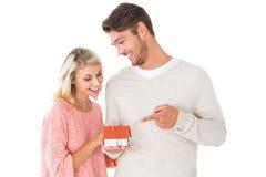 拿着微型房子模型的有吸引力的夫妇 免版税库存照片