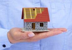 拿着微型房子的手 免版税库存照片