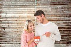 拿着微型房子的有吸引力的夫妇的综合图象塑造 库存图片