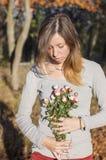 拿着微型玫瑰的愉快的深色的女孩 免版税库存照片