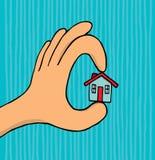 拿着微小的房子的手 免版税库存照片