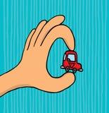 拿着微小的汽车的手 免版税库存照片