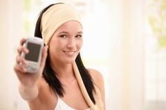 拿着微笑妇女年轻人的移动电话 图库摄影