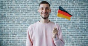 拿着德国旗子和微笑在砖墙背景的愉快的人画象 股票视频