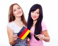 拿着德国旗子的两个微笑的女孩 库存照片