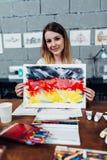 拿着德国旗子的绘画创造性的年轻女性设计师显示坐在时髦的车间的一个新的印刷品想法 库存照片