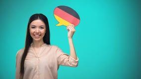 拿着德国旗子讲话泡影的微笑的女孩,学会语言,旅行想法 股票视频