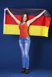 拿着德国的一面大旗子的年轻美丽的妇女 免版税库存照片