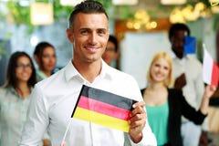 拿着德国的旗子的愉快的商人 免版税库存图片