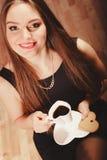 拿着心形的咖啡杯的微笑的妇女 免版税库存照片